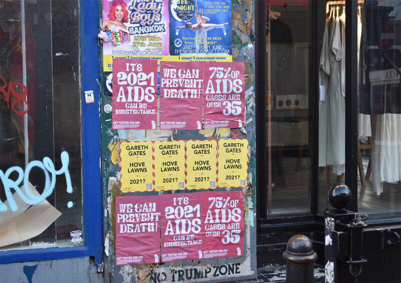 Photo of posters on a shop window encouraging AIDS testing, and older posters