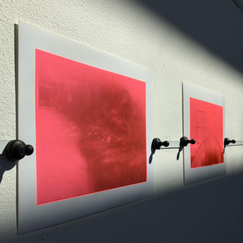 Two gelatin silver prints, hung on a wall, red in colour with dark sections.