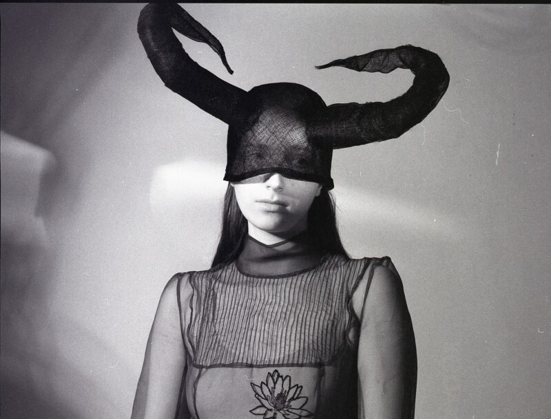 black and white photo of a woman wearing veiled horns
