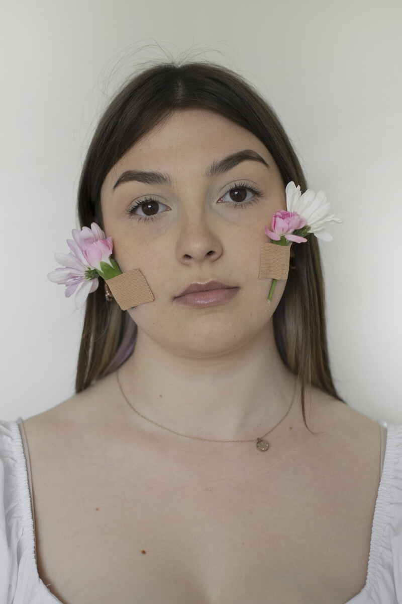 woman with flowers taped on her face