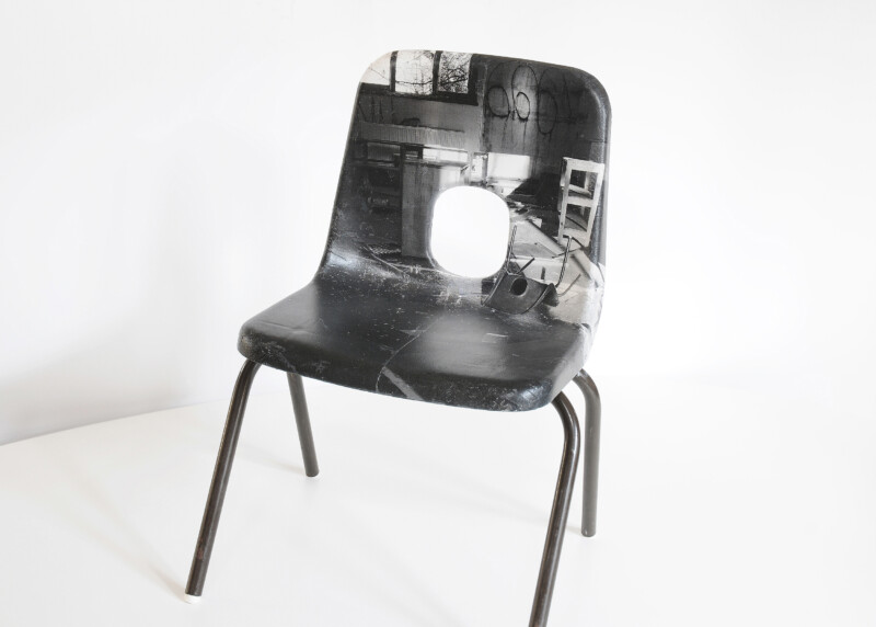 A plastic chair that is covered with a black and white image of a dilapidated classroom