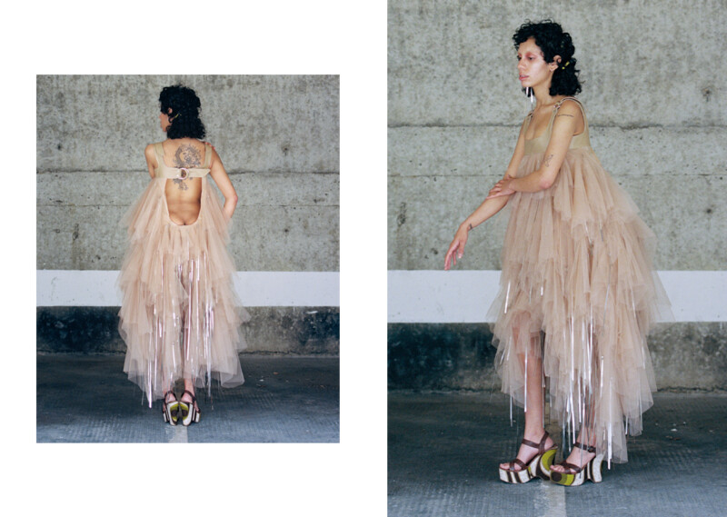Two photos of a model wearing a beige, ruffled dress, cut low at the back, with lengths of a decorative metallic material hanging from it.