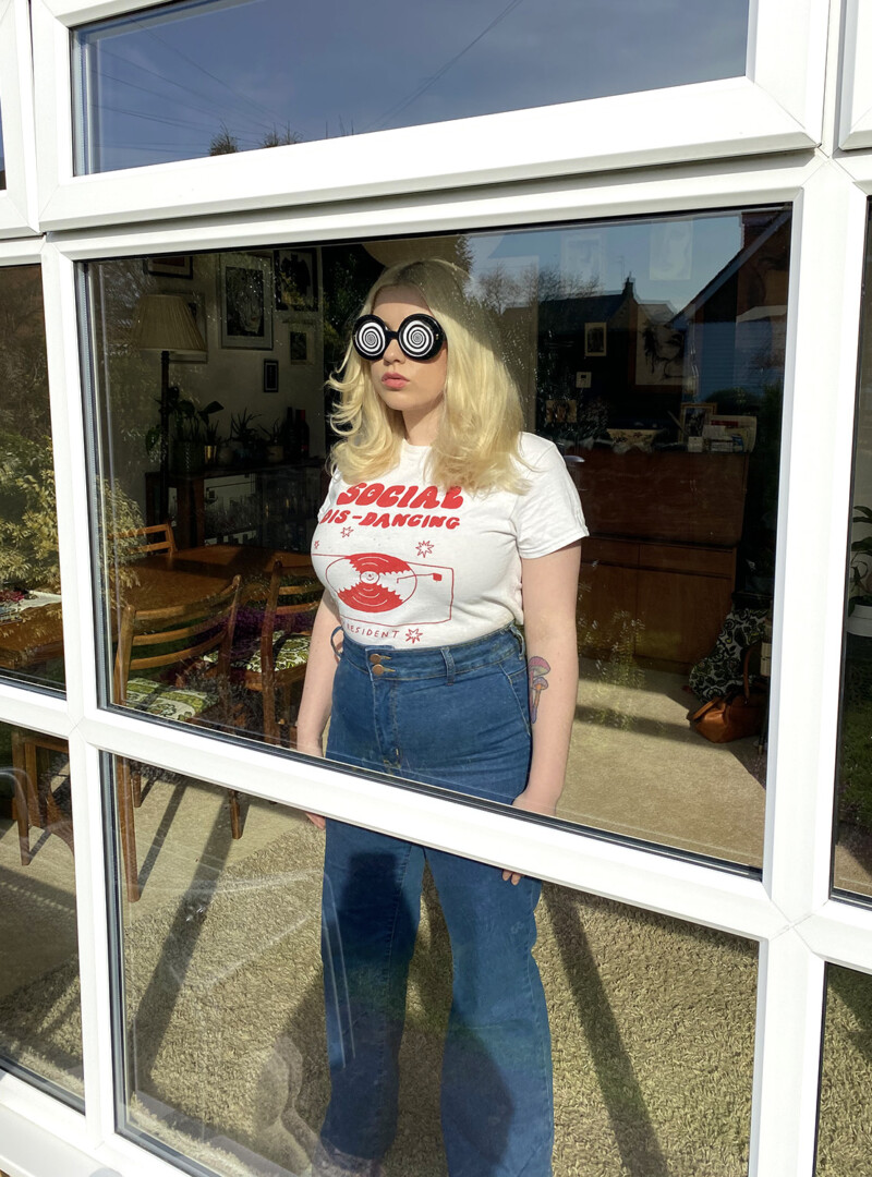 person with spiral sunglasses looking through window