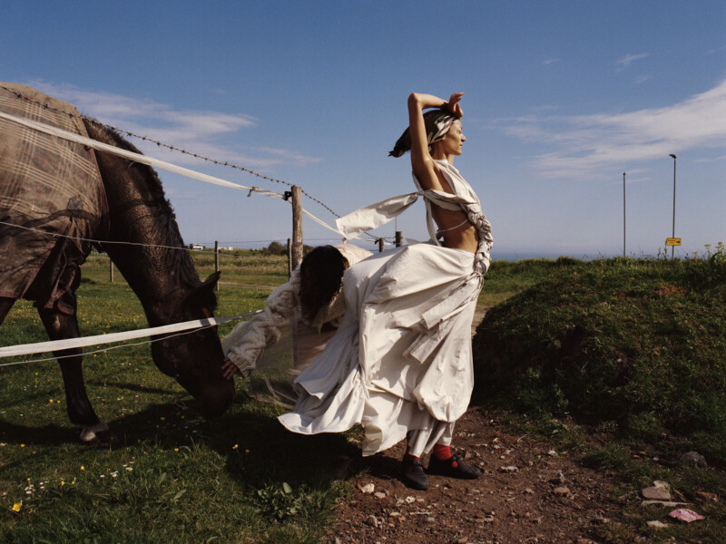 women wearing concept clothing next to a horse
