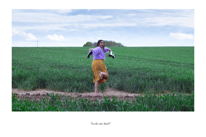A Woman looking shocked holding her shoes in a field