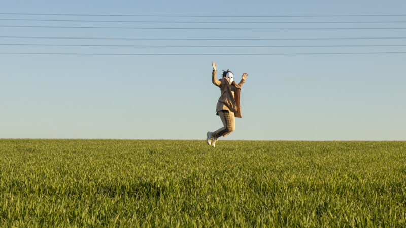 a man in a mask jumping in a field