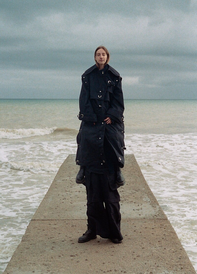 tall person wearing long jacket with multiple pockets on a groin in the sea