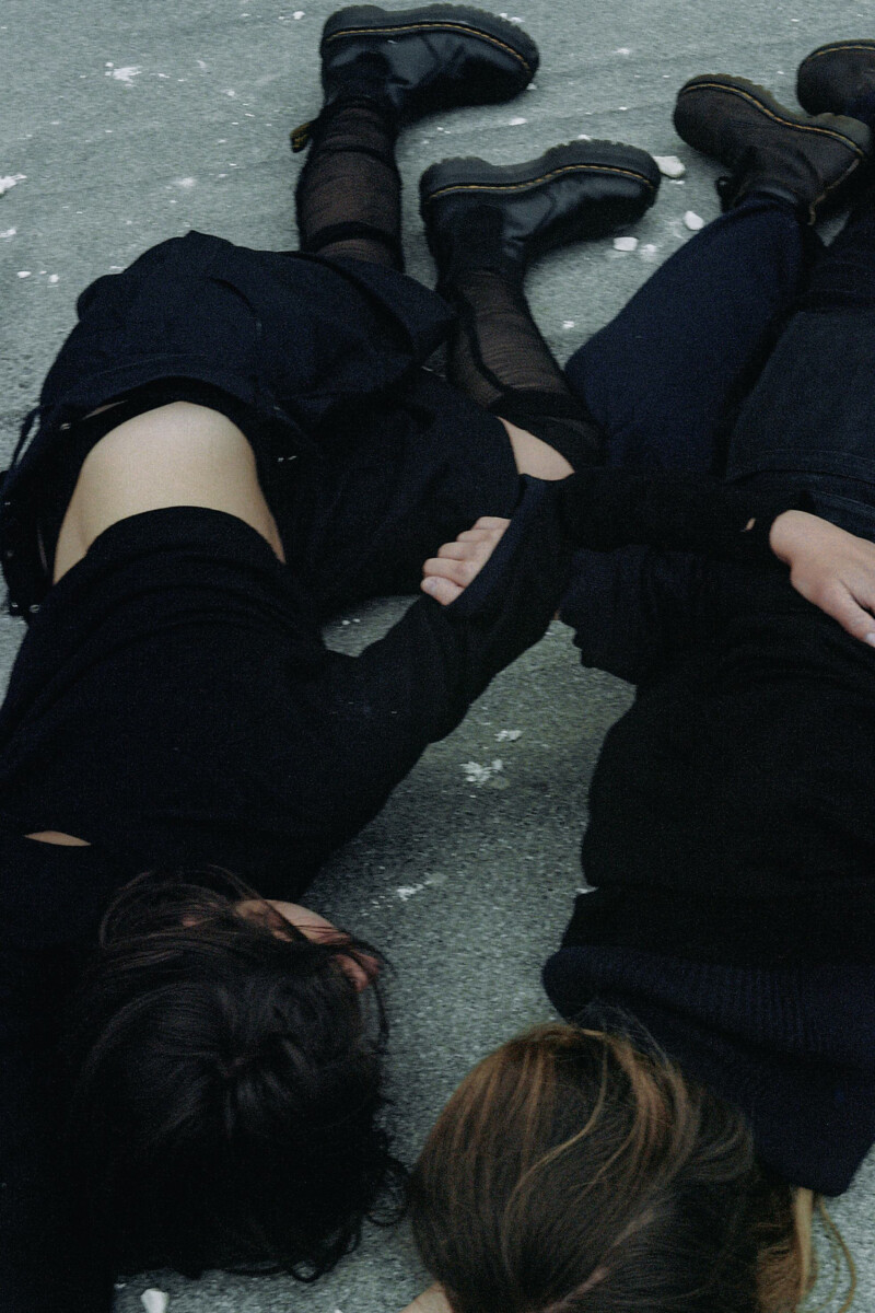 image of people wearing black with linked arms on the floor
