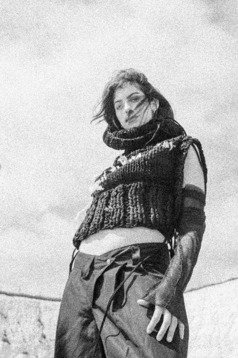 black and white image of person wearing knitted crop top and canvas trousers