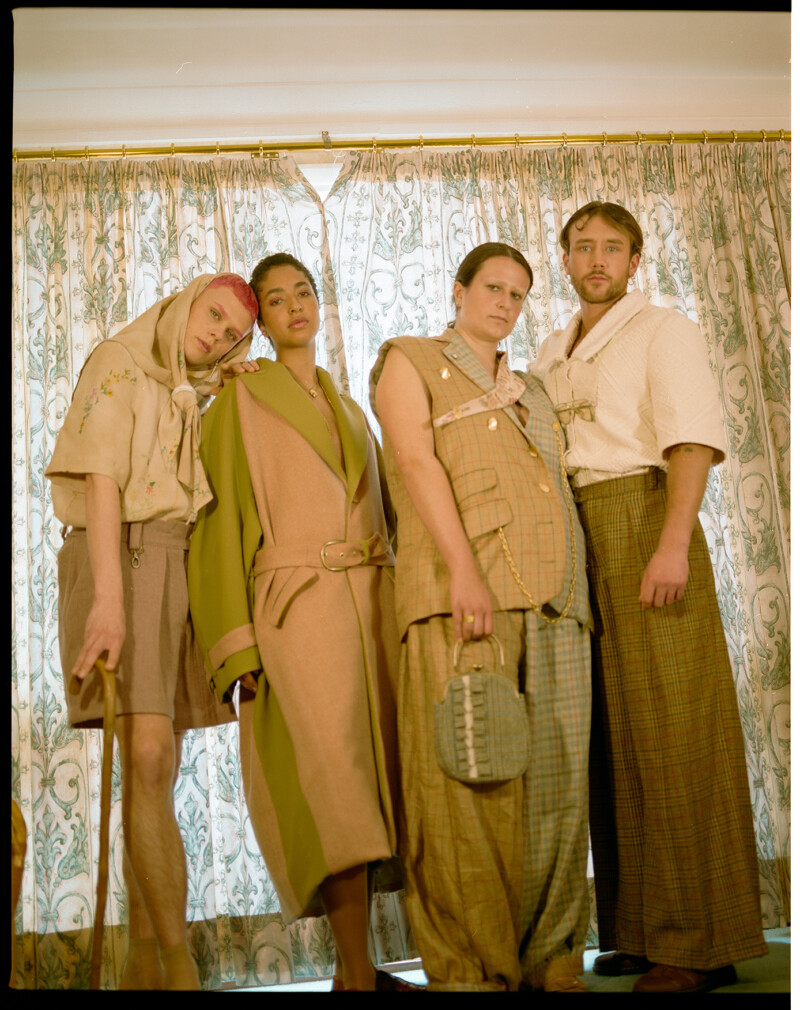 Photograph of four models standing in front of a curtained window wearing contemporary fashion designs made from recycled materials and clothing.