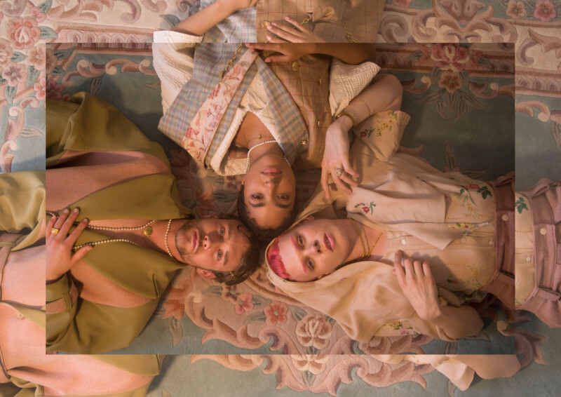 Photograph of three models lying on their backs on a rug wearing contemporary fashion designs made from recycled materials and clothing.