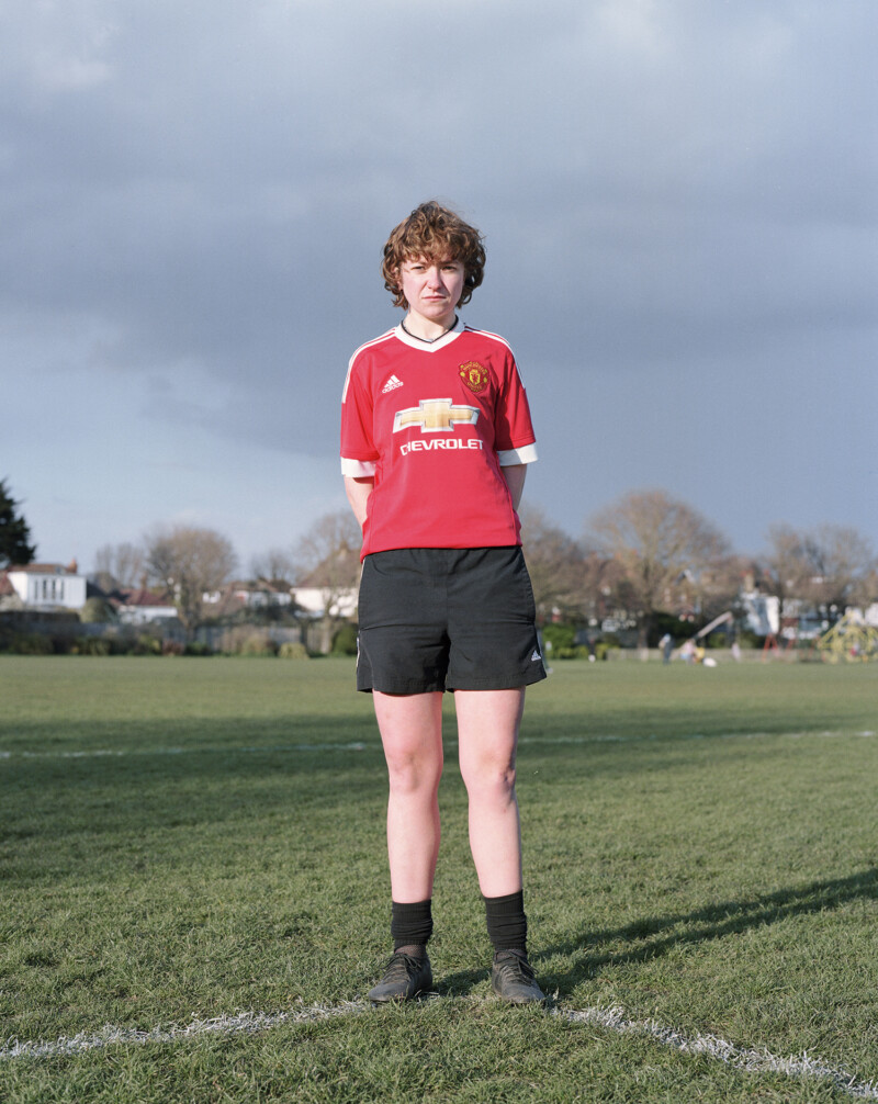 person in red football top and black shorts