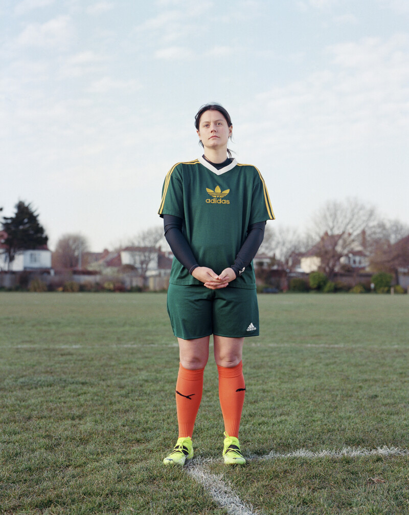 person in green football top and shorts with orange socks