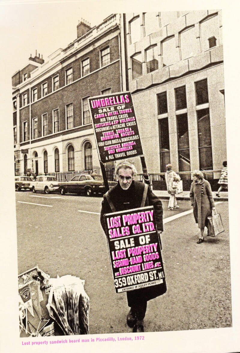 photo of man with walking billboard with pink text