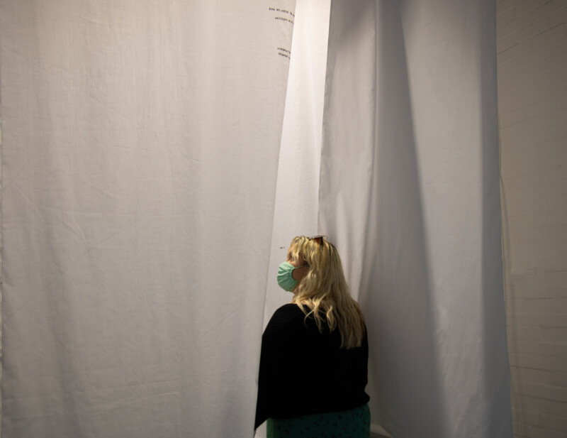 Person standing inside installation of hanging white sheets