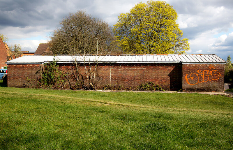 Photo of single story red brick building with grassed area in front. Graffiti and painted goalposts on wall of the building.