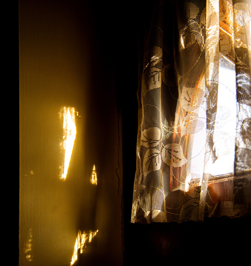 Photo of a net-curtained window with sunlight passing through on to a wall