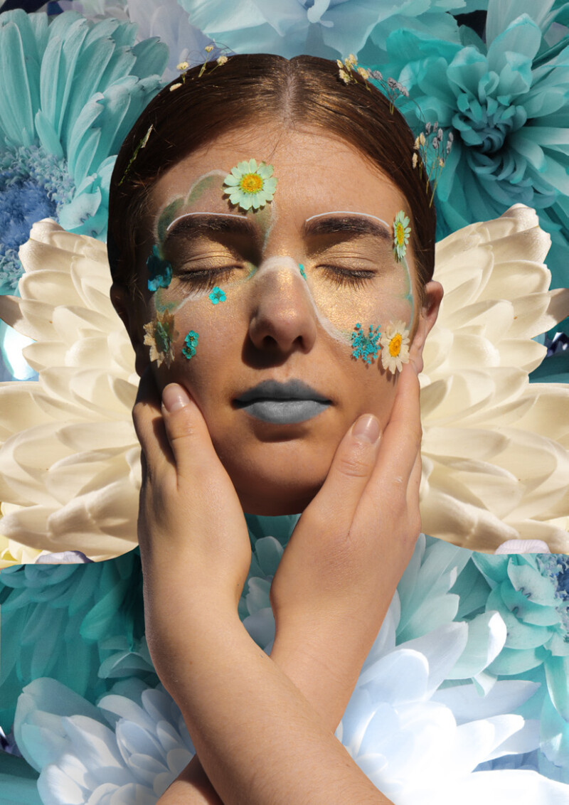 person surrounded by blue and white flowers with blue tinted makeup and pressed flowers on face with hands holding their face