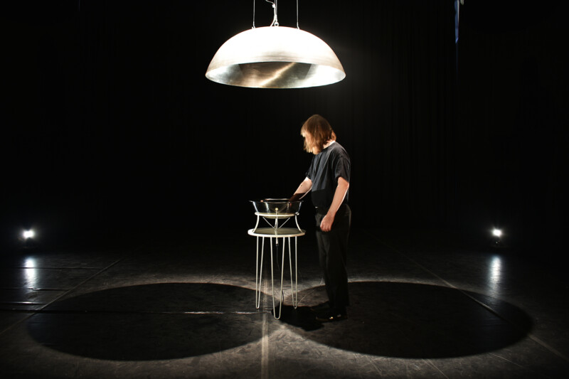 Installation with a woman with her hands in a large bowl, a domed light is above her
