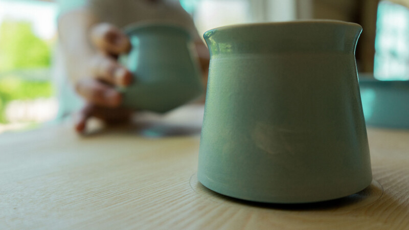closeup of green ceramic mug with one being lifted out of place in the background