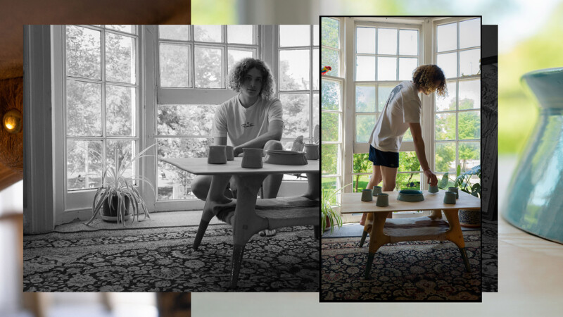 Cellan crouching behind his table with ceramics in position and Cellan reaching down to table to pick up ceramic vessel