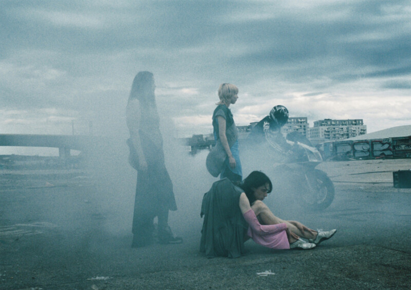 Photograph of models wearing contemporary fashion designs, in an urban setting, with a motorbike and rider in the rear, with smoke and fumes purmeating the shot.