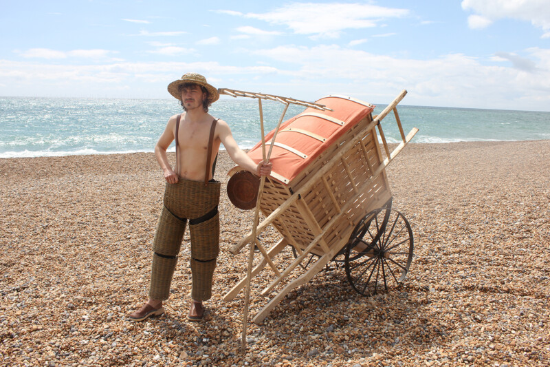 person wearing wicker trousers and holding a wooden rake in front of a cart on a beach