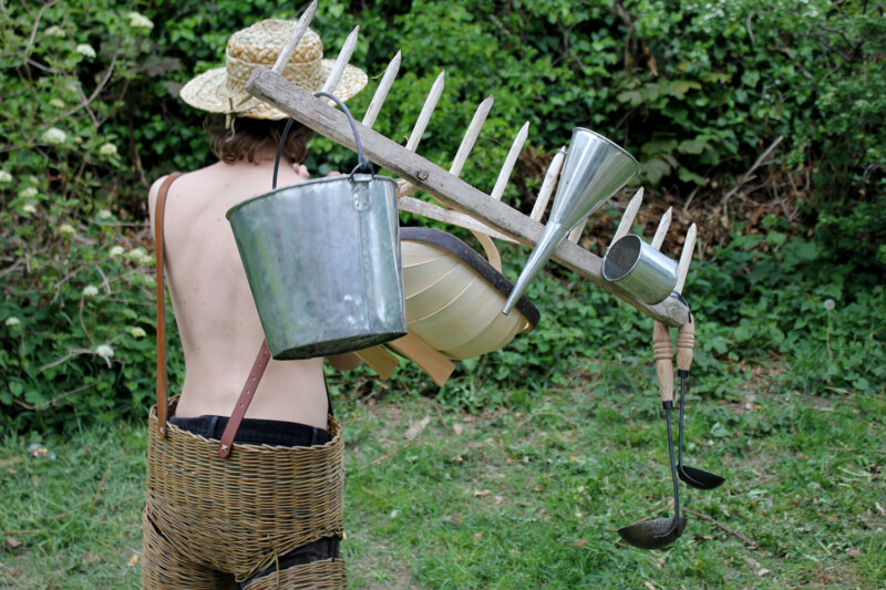 Person carrying garden tools in wicker trousers