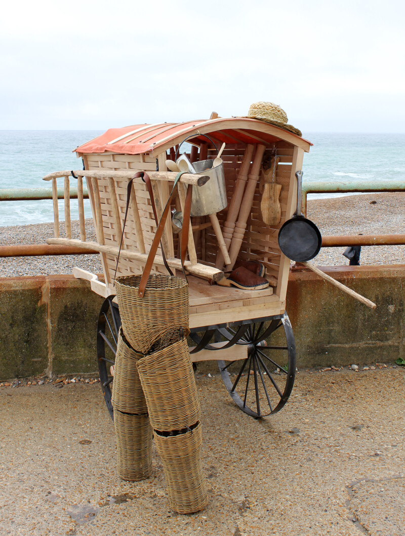 a cart with a range of tools and wicker trousers hanging on it