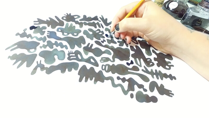 Photo of the artist creating an artwork with black ink