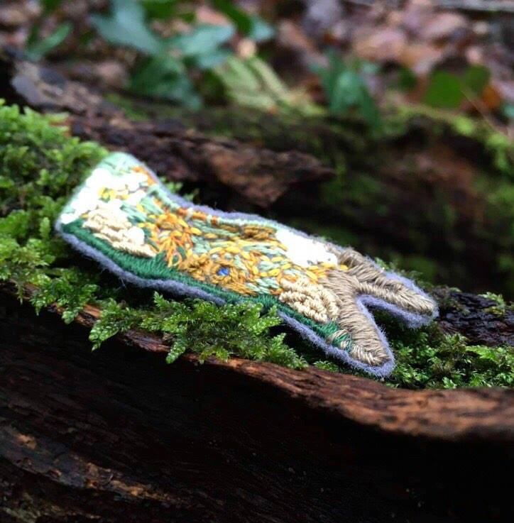An hand-embroidered work photographed in woodland