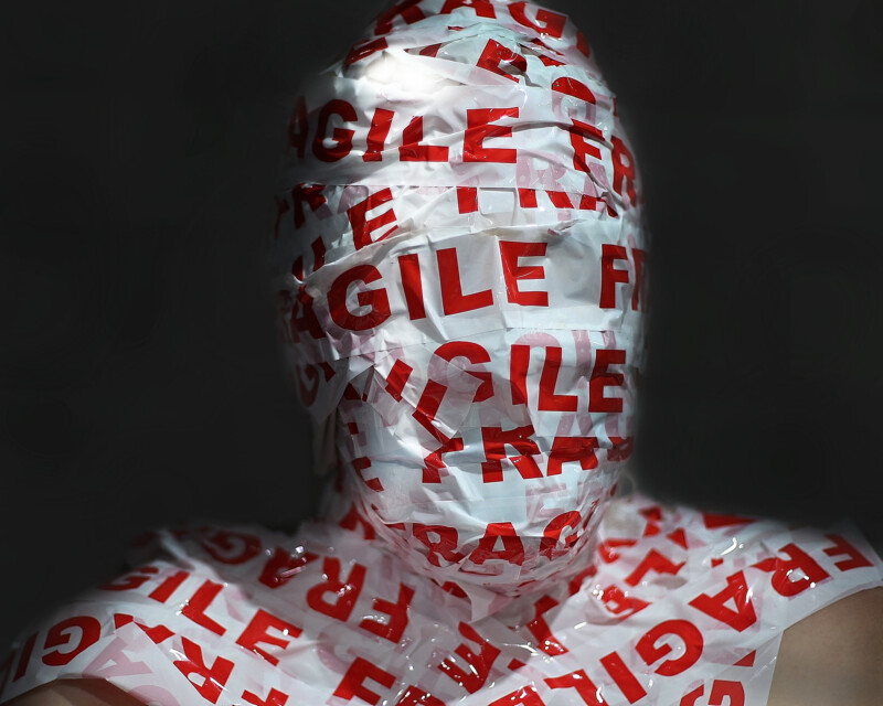 Photograph of a person's head and shoulders covered in 'Fragile' packing tape.