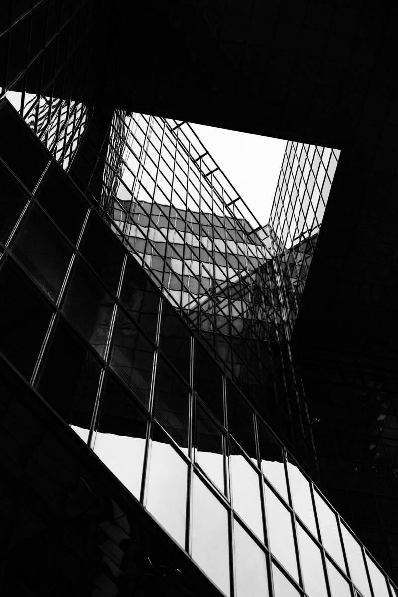 Black and white photograph of London city buildings: office / high-rise buildings with windows / shadow / reflection and high contrast.