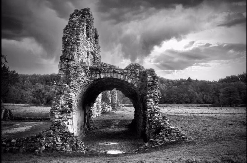 Black and white photograph of an ancient ruin againsy a dramatic skyline.